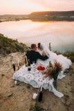 La vue extérieure arrière des nouveaux mariés touche des nez derrière le pique-nique réglé près de la rivière Photo libre de droits