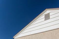 La vue générique de maison du bord de côté et de toit, du stuc et du vinyle avec la ventilation de grenier a placé contre un ciel image stock