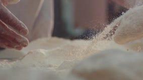 La vue haute étroite d'extrémité des baker's remet un malaxer les morceaux de pâte dans la farine sur la table Beau banque de vidéos
