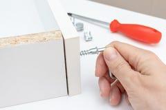 La vue haute ?troite d'une personne assemblant le nouveau tiroir blanc utilisant un tournevis, serrent une vis avec une cl? d'All image stock