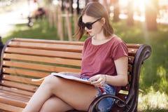 La vue horizontale de l'étudiant sérieux utilise les lunettes de soleil à la mode, T-shirt occasionnel et les shorts de treillis, photographie stock