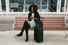La vue horizontale de la femme afro-américaine joyeuse se repose sur le banc et textote par l'intermédiaire du téléphone portable Image stock