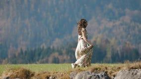 La vue horizontale en gros plan de la fille dans la longue robe appréciant le temps gratuit dans les montagnes au printemps clips vidéos