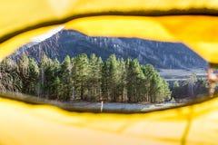 La vue hors de la tente à l'arbre et les montagnes aménagent en parc Image stock