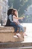 La vue intégrale des amies magnifiques s'asseyant sur la fontaine et prenant des selfies utilisant le selfie collent Photos stock