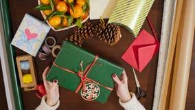 la vue 4K supérieure de ci-dessus du ` s de Madame remet décorer le cadeau de Noël avec le ruban Photos libres de droits