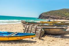 La vue large du groupe de bateaux de pêche s'est garée en bord de la mer avec les personnes et la falaise à l'arrière-plan, Visak Photo libre de droits