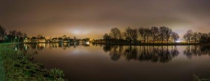 La vue panoramique paisible de la rivière et des arbres éclairés à contre-jour par la ville d'Amsterdam s'allume image stock