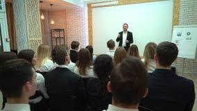 La vue par derrière d'un groupe d'étudiants dans une salle de classe, écoutant en tant que leur professeur tient une conférence U banque de vidéos