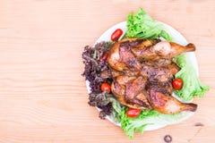La vue plate supérieure sur le poulet rôti grillé juteux avec l'herbe, la salade et la tomate garnissent Photographie stock libre de droits