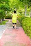 La vue rare du jeune garçon asiatique fonctionnent dans le jardin photos libres de droits