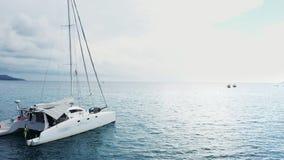 La vue a?rienne d'une bo?te ancr?e de position et de personnes de yacht de catamaran prenant un bain de soleil l?-dessus est plat banque de vidéos