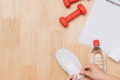 La vue a?rienne de la femme remet attacher des chaussures avec des ?quipements de sport sur le fond en bois photos libres de droits