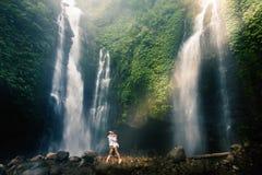 La vue romantique étonnante des couples heureux s'approchent de la belle cascade grande Photo stock