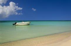 La vue romantique du bateau blanc sur l'océan azuré contre le ciel bleu parfait et l'or poncent la plage Image stock
