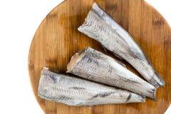 La vue supérieure au-dessus des merluches crues fraîches pêchent sur le conseil cuting avec l'espace blanc de copie Photographie stock libre de droits