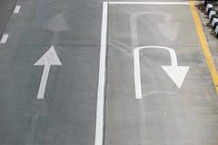 La vue supérieure avec les flèches droites blanches et l'U tournent des flèches sur la route Photographie stock libre de droits
