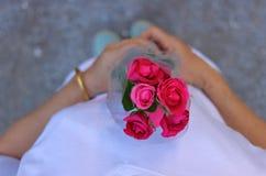 La vue supérieure d'un beau bouquet des roses rouges est partagée en main de la femme âgée par milieu avec le fond blanc de chemi Photographie stock