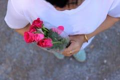 La vue supérieure d'un beau bouquet des roses rouges est partagée par la femme âgée par milieu Jour du ` s de Valentine ou concep Photographie stock