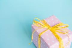 La vue supérieure d'un boîte-cadeau enveloppé dans le rose a pointillé le papier et a attaché l'arc jaune au-dessus du fond bleu- Photo libre de droits