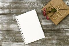 La vue supérieure d'un cadeau enveloppé en papier de métier et un journal intime ou un carnet et sec a monté fleur sur une table  image stock
