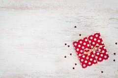 La vue supérieure d'un rouge a pointillé le boîte-cadeau au-dessus du fond en bois blanc Copiez l'espace Images stock