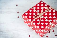 La vue supérieure d'un rouge a pointillé le boîte-cadeau au-dessus du fond en bois blanc Copiez l'espace Image libre de droits