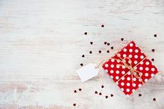 La vue supérieure d'un rouge a pointillé le boîte-cadeau au-dessus du fond en bois blanc Copiez l'espace Note vide Paillettes en  Image stock
