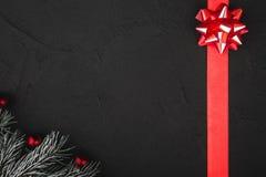 La vue supérieure supérieure d'un ruban rouge et l'arbre s'embranchent sur un fond noir en pierre Photographie stock libre de droits