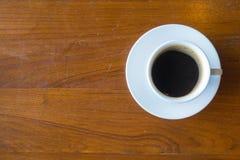 La vue supérieure d'une tasse de café chaud a mis dessus le vieux backgrou en bois de table Photos stock