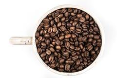 La vue supérieure d'une tasse a rempli de grains de café photos stock