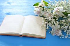 La vue supérieure de la belle disposition de fleurs blanche et vident le carnet ouvert au-dessus du fond en bois bleu Copiez l'es Image stock