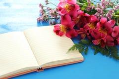 La vue supérieure de la belle disposition de fleurs rouge et vident le carnet ouvert au-dessus du fond en bois bleu Copiez l'espa Photographie stock