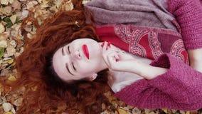 La vue supérieure de la belle fille avec des mensonges rouges de cheveux au-dessus des feuilles sèches tient une cendre de montag Photos libres de droits