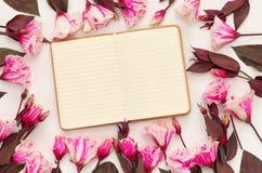La vue supérieure de belles fleurs et ouvrent le carnet vide Photos stock