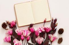 La vue supérieure de belles fleurs et ouvrent le carnet vide Photo stock