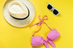 La vue supérieure de deux morceaux de rose a quadrillé le costume de natation, les lunettes de soleil blanches et le chapeau de p Images stock