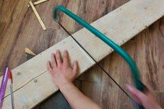 La vue supérieure de la femme remet scier une planche en bois à l'intérieur concepts image stock