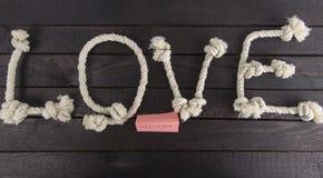 La vue supérieure de la forme d'amour avec la corde et le mot finissent sur le fond en bois Image stock