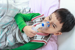 La vue supérieure de l'enfant asiatique fâché tient un inhalateur de vapeur de masque pour le tre Image libre de droits