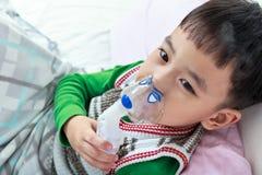 La vue supérieure de l'enfant asiatique tient un inhalateur de vapeur de masque pour le traitement Photos stock
