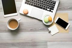 La vue supérieure de l'espace de travail avec le macaron et le café pendant le temps se cassent Images libres de droits