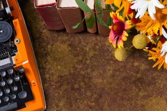 La vue supérieure de l'espace de travail de la machine à écrire orange de vintage et sur le bouquet de l'été orange fleurit Photo stock