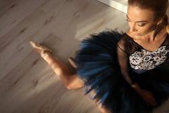 La vue supérieure de la ballerine professionnelle dans des chaussures bleues de tutu et de pointe se reposent sur le plancher Cop Image stock