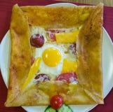 La vue supérieure de la crêpe délicieuse avec la saucisse de Bologna, le fromage de cheddar, l'oeuf et le salami a servi d'un pla Photos stock
