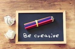 La vue supérieure de la pile chiffonnée de papier et de crayons au-dessus du tableau noir avec l'expression soit créative Images libres de droits