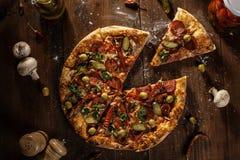 La vue supérieure de la pizza cuite au four fraîche avec la tranche a servi images stock