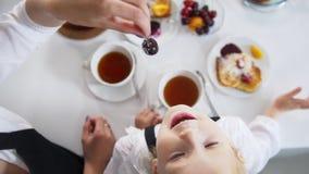 La vue supérieure de la mère et de sa petite fille le temps de thé mange du fruit clips vidéos
