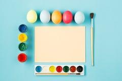 La vue supérieure de Pâques sur le lieu de travail bleu de bureau de table Photos stock
