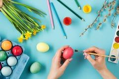 La vue supérieure de Pâques sur le lieu de travail bleu de bureau de table Images libres de droits
